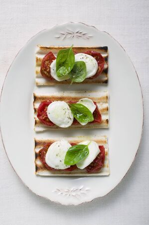 substantial: Three tomato and mozzarella toasts with basil LANG_EVOIMAGES