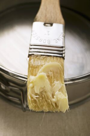 greasing: Pastry brush with butter in front of baking tin