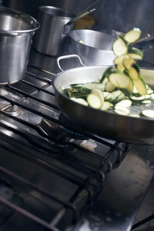 sautee: Tossing courgette slices in frying pan