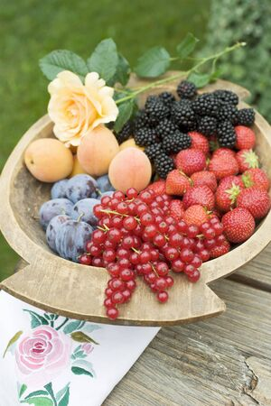 Plums, apricots and berries in wooden bowl