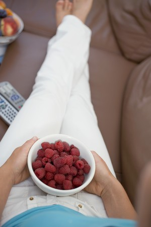 well beings: Woman watching TV holding bowl of fresh raspberries LANG_EVOIMAGES