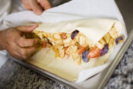 rolling up: Making fruit strudel: rolling up the strudel