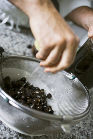 the draining: Draining black olives in a sieve LANG_EVOIMAGES