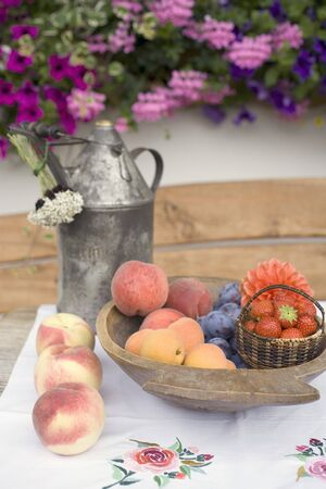 front house: Summer fruit still life on table in front of house