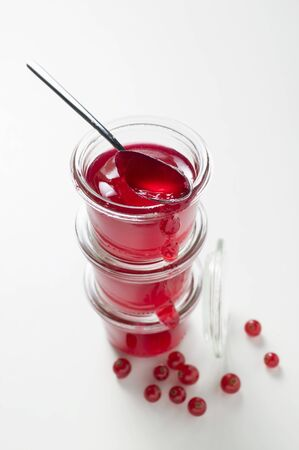 redcurrant: Three jars of redcurrant jelly, one opened, with spoon