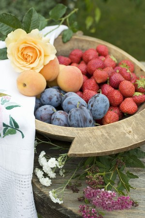 Plums, strawberries and apricots in wooden bowl LANG_EVOIMAGES