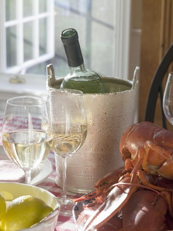 chilled out: White wine bottle in ice bucket, wine glasses, lobster, lemon