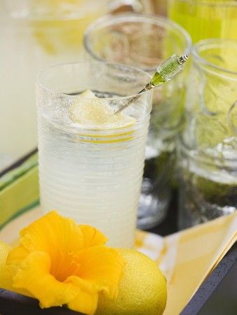 soda pops: Glass of lemonade, lemon and flower on tray