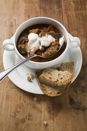 substantial: Goulash soup with sour cream in soup cup, slices of bread LANG_EVOIMAGES