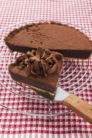 chocolate tart: Chocolate tart on cake rack and piece on cake server LANG_EVOIMAGES