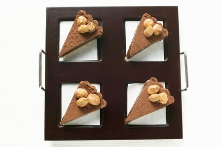 chocolate tart: Four pieces of chocolate tart with almonds on tray
