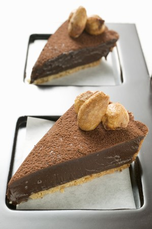 chocolate tart: Two pieces of chocolate tart with almonds on tray