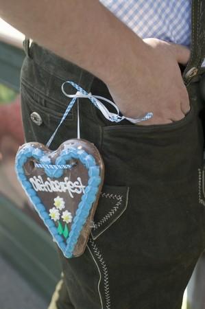 lederhosen: Man with Lebkuchen heart on his lederhosen at Oktoberfest