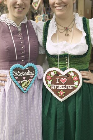conviviality: Two women in national dress with Lebkuchen hearts at Oktoberfest