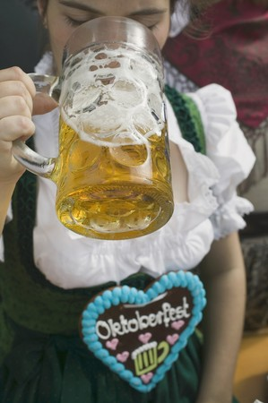 20 to 25 year olds: Woman drinking litre of beer at Oktoberfest LANG_EVOIMAGES