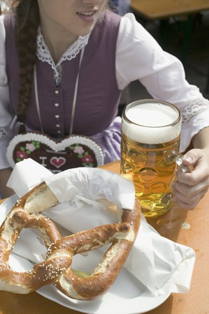 litre: Woman with litre of beer and pretzel at Oktoberfest LANG_EVOIMAGES