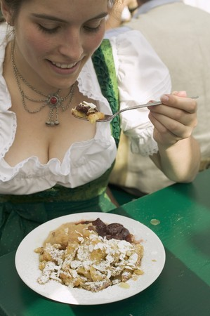 20 to 25 year olds: Woman eating scrambled pancake with plum compote at Oktoberfest