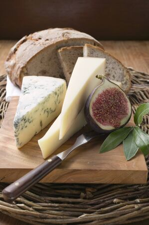 several breads: Various types of cheese, bread and half a fig