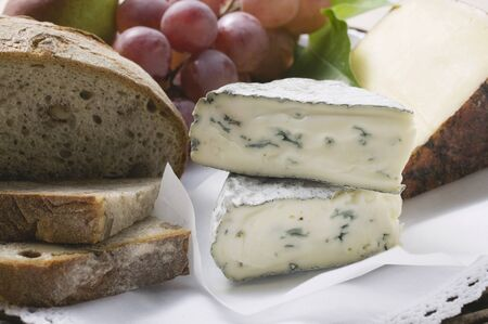 Two different types of cheese, red grapes and bread