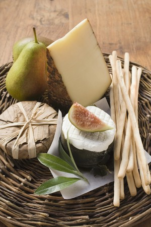 breadstick: Cheese still life with pears, fig & grissini on wicker plate LANG_EVOIMAGES