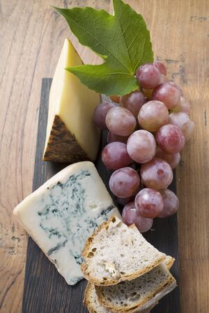 several breads: Pieces of Appenzeller and blue cheese, red grapes, bread LANG_EVOIMAGES
