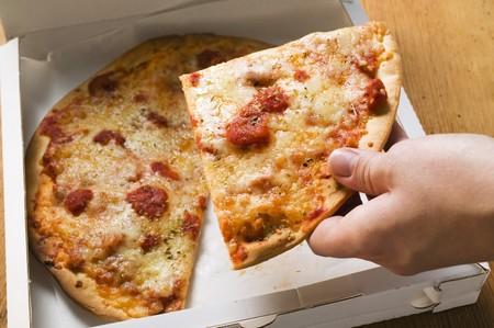 pizza box: Mano que toma una porci�n de pizza Margherita de caja de pizza