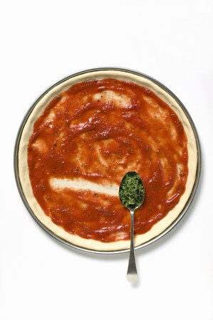 pizza base: Pizza base with tomato sauce and spoonful of oregano