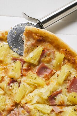 pizza cutter: Hawaiian pizza, sliced, in pizza box with pizza cutter LANG_EVOIMAGES