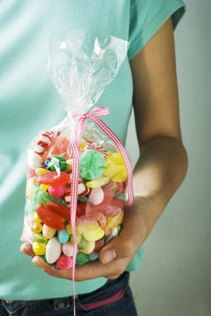 cellophane: Hand holding cellophane bag of coloured sweets