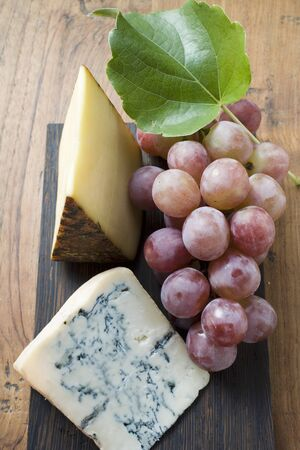 appenzeller: Pieces of Appenzeller and blue cheese with red grapes