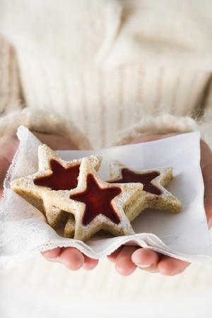 jam biscuits: Hands holding jam biscuits on napkin