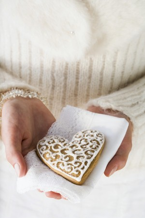 christmassy: Hands holding gingerbread heart on napkin (Christmassy) LANG_EVOIMAGES