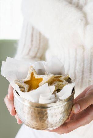 jam biscuits: Mani che tengono marmellata biscotti in una ciotola d'argento LANG_EVOIMAGES