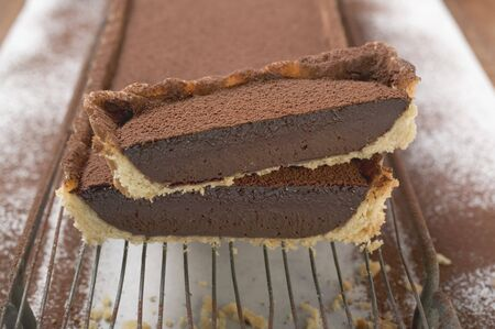 chocolate tart: Rectangular chocolate tart with cocoa powder, partly sliced