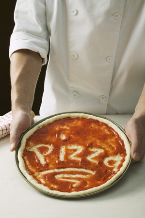 pizza base: Pizza base spread with tomato sauce, with the word Pizza