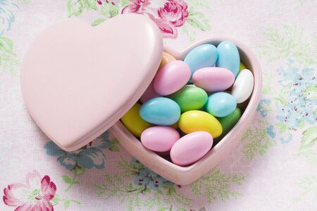 sugared almonds: Coloured sugared almonds in pink heart-shaped dish LANG_EVOIMAGES