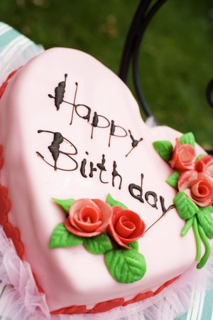 open air: Pink heart-shaped birthday cake on chair in the open air LANG_EVOIMAGES