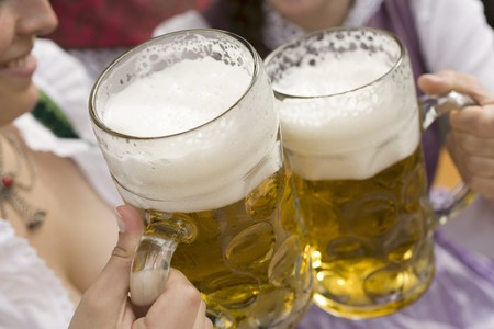 conviviality: Hands clinking litres of beer together (Oktoberfest, Munich)