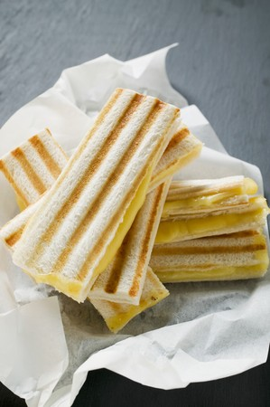 qs: Several toasted cheese sandwiches on paper