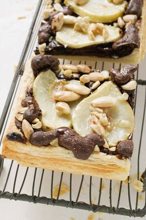 chocolate tart: Two pieces of pear & chocolate tart with almonds on cake rack LANG_EVOIMAGES