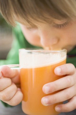 well beings: Child drinking a glass of freshly pressed apple juice