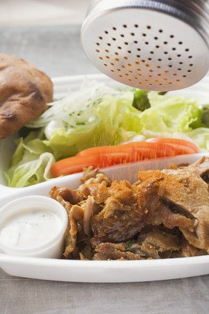 lunch tray: Sprinkling seasoning on d�ner kebab in lunch tray