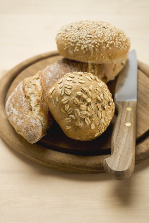 several breads: Baguette and wholemeal rolls on breadboard with knife LANG_EVOIMAGES
