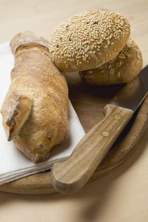 Baguette & wholemeal bread rolls on breadboard with knife