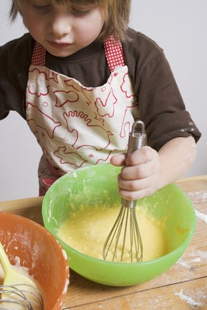 stirring: Small boy stirring cake mixture with whisk