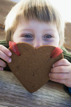 christmassy: Small boy with Christmassy gingerbread heart LANG_EVOIMAGES