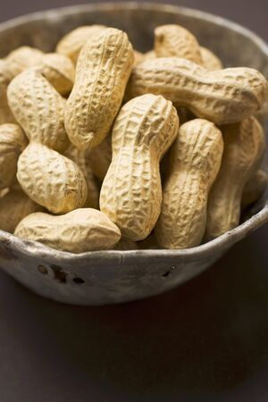 unpeeled: Several peanuts in a bowl LANG_EVOIMAGES