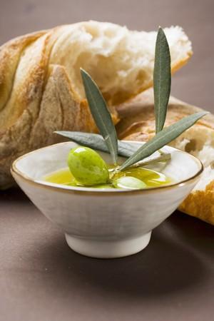 several breads: Olive sprig with green olives in bowl of olive oil, white bread LANG_EVOIMAGES