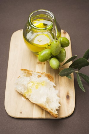 several breads: Olive sprig with green olives, white bread and olive oil