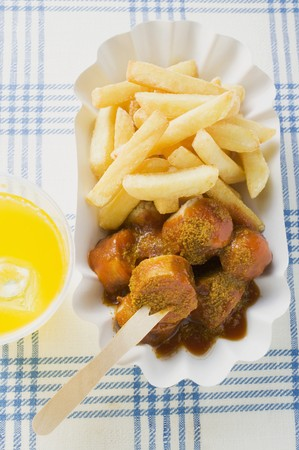 Sausage with ketchup & curry powder & chips in paper dish, lemonade LANG_EVOIMAGES